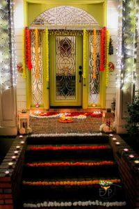 Festive Diwali Home Entrance Decor using rangoli made from flowers and diyas.