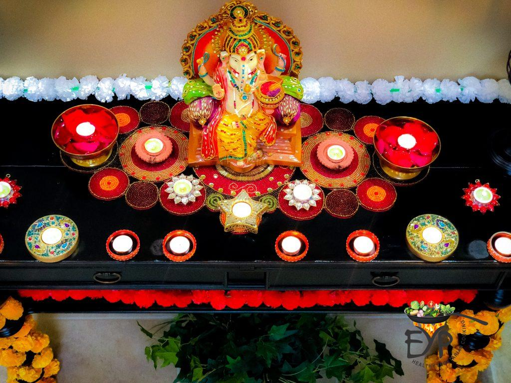 Home Diwali Festive indian Decor Idea with Ganesh Idol, candles, flowers and table mets