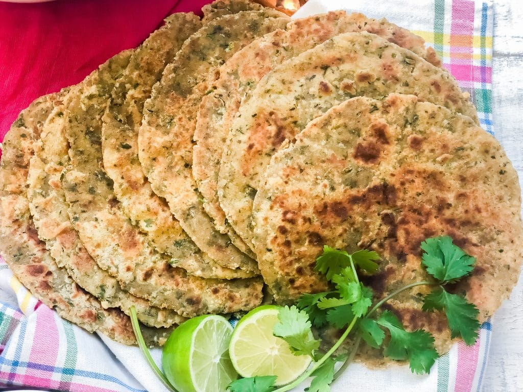 Cilantro Paneer Paratha shown with cut lemon and cilantro sprig.