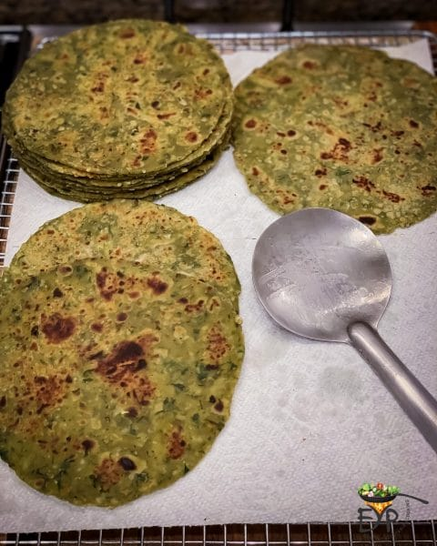 cooked paratha on cooling rack layered with kitchen paper towel
