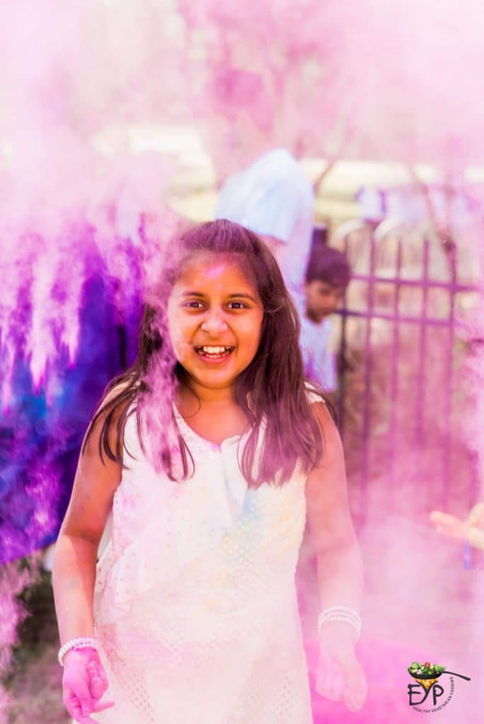 Young girl tossing Holi colors in the air