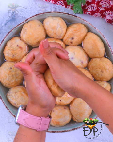Gently squeezing water out of soaked vada