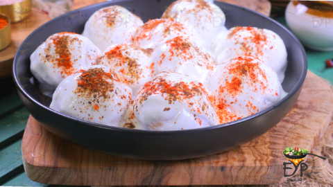 Dahi vada with spices sprinkled on top