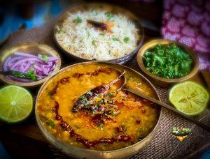 Dal Tadka served in a copper bowl with accompaniments including rice
