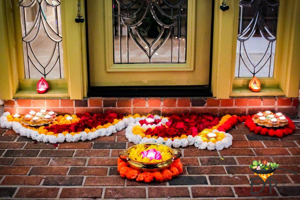 Flower rangoli and home main entrance door
