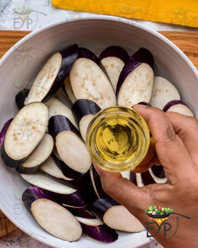 Avacado oil being being added to sliced eggplant