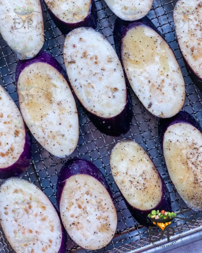 closeup of seasoned eggplant on air-fryer tray