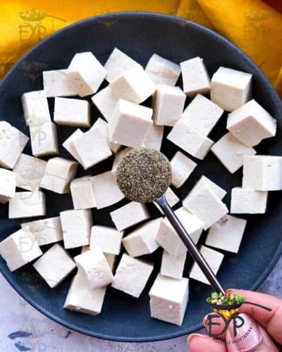 black pepper being sprinkled on Tofu