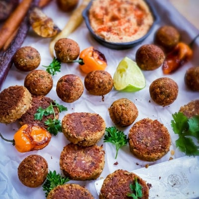 Falafel burger patties and roundels on a plate with humus and other accompaniments