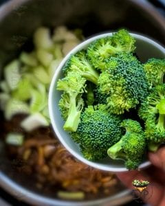 Broccoli being added to japchae recipe