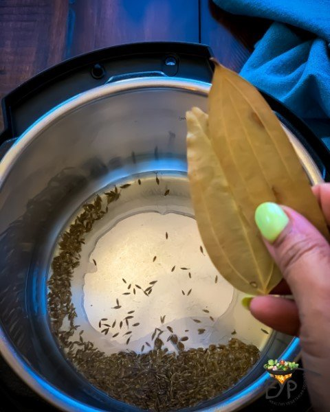 bay leaves being added to instant pot pan for jeera rice recipe