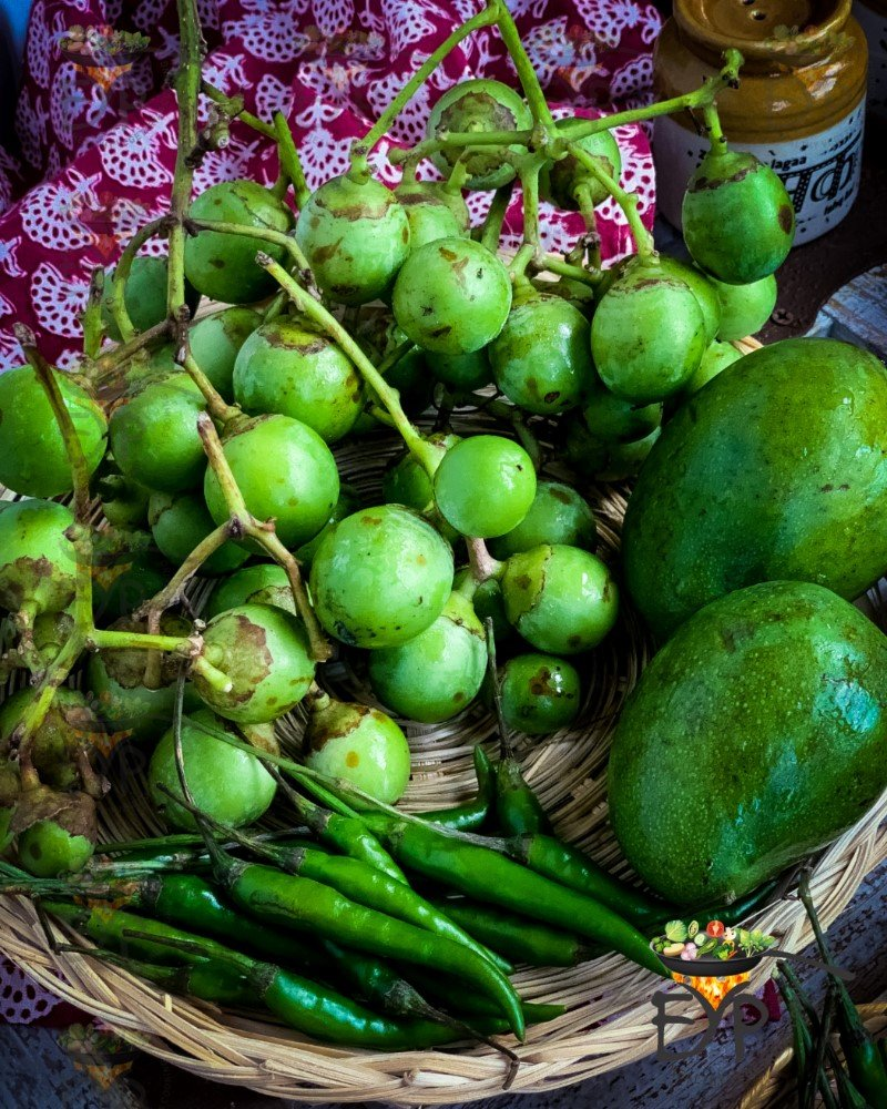 Lasoda in basket with green mango and green chillies.