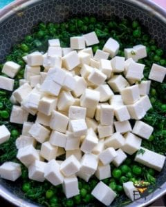 Paneer cubes being added to recipe