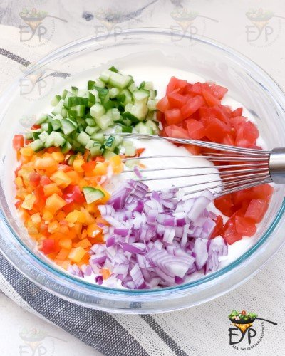 Vegetables being added to yogurt for raita