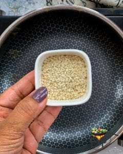 Sesame seeds being added to pan to roast