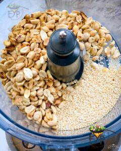 Roasted peanuts and sesame seeds being added to food processor jar