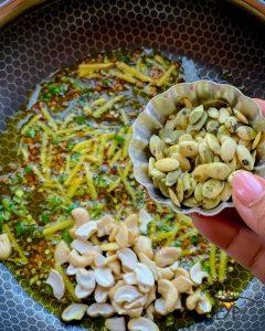 Pumpkin seeds being added to pan