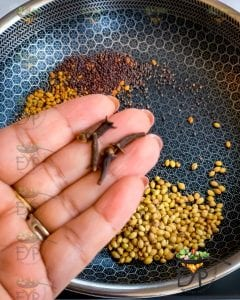 cloves being added to pan for roasting