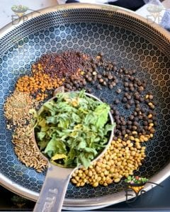 dry fenugreek leaves being added to pan