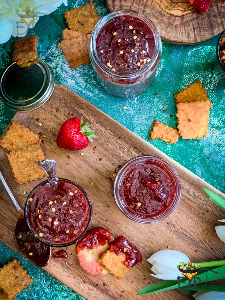 Top down view of Strawberry ginger chutney in a jar decorated on a platter.