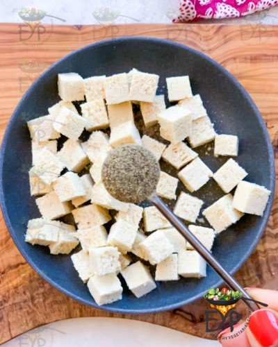 Black Pepper being sprinkeled on chopped tofu