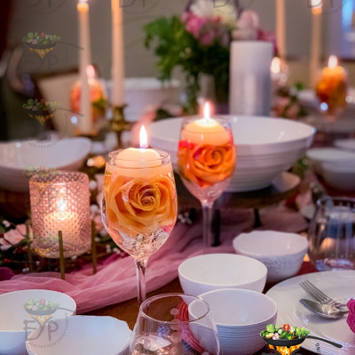Wine glasses with floating candles and rose for valentine day table setting
