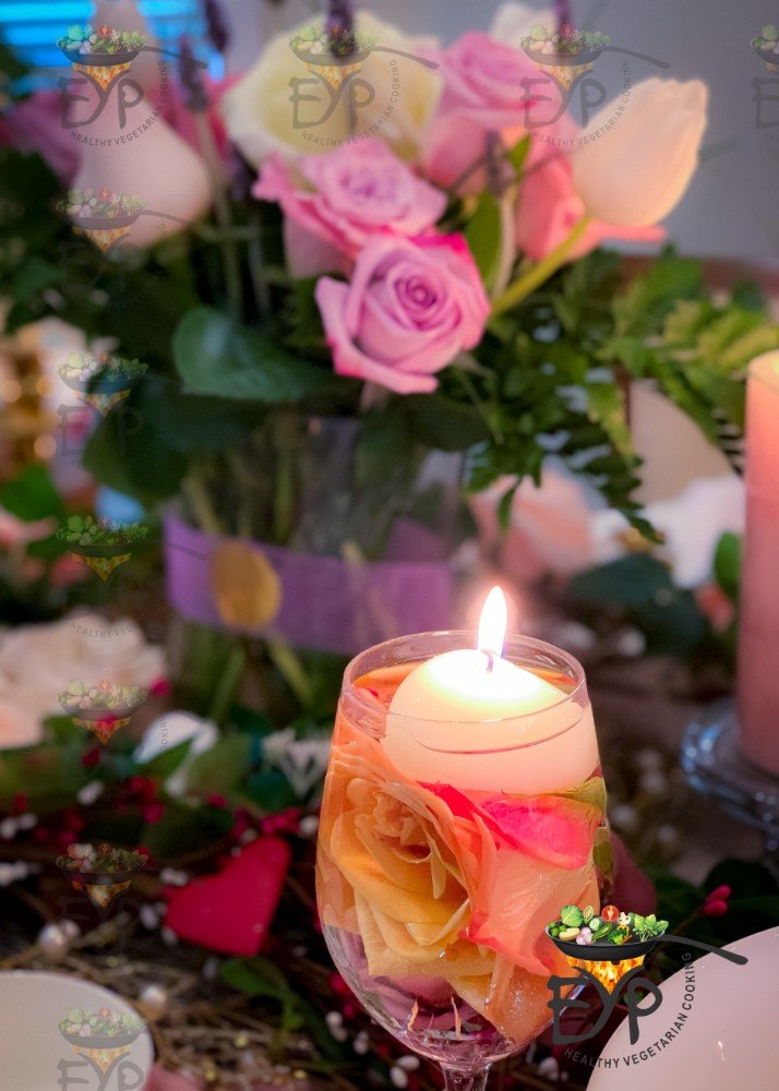 closeup of a wine glass floating candle with rose