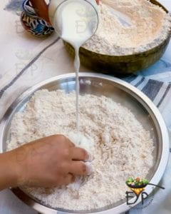Warm milk being added to flour for roti dough