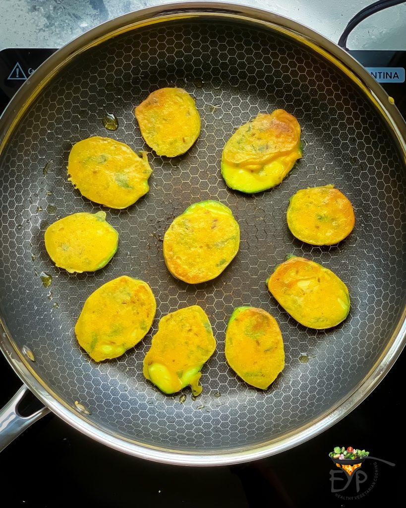 zucchini fritter being crisped on the pan
