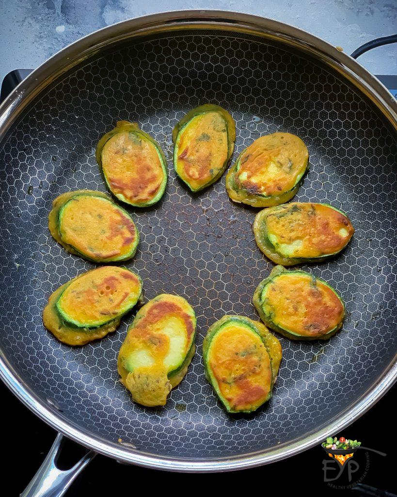 zucchini fritters being crisped on the pan