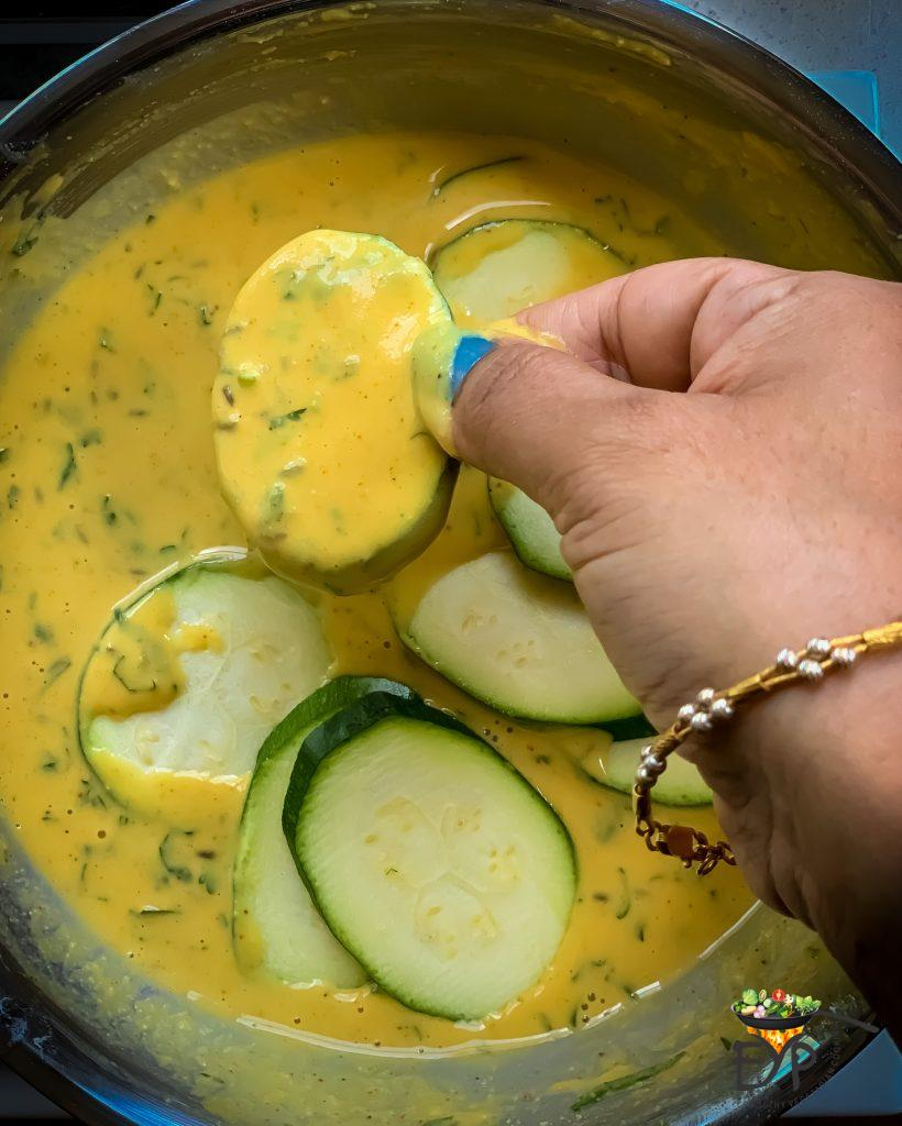 sliced zucchini being dipped in batter before being placed on a pan