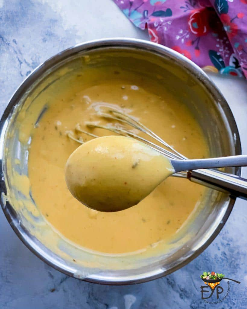 Checking batter consistency using a spoon