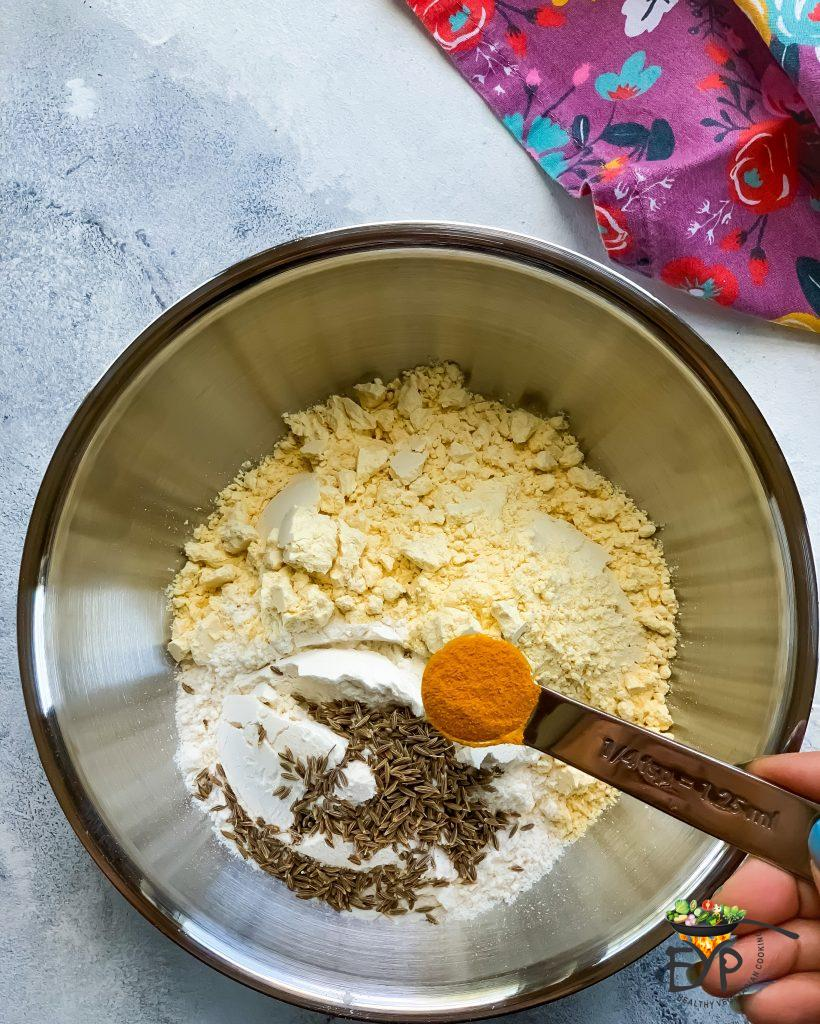 turmeric powder being added to bowl